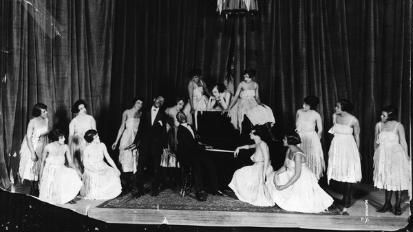 American composers and musicians Noble Sissle, center left, and Eubie Blake, on piano, perform with a group of women on stage in the early 20th century. Sissle and Blake wrote the score for Shuffle Along.