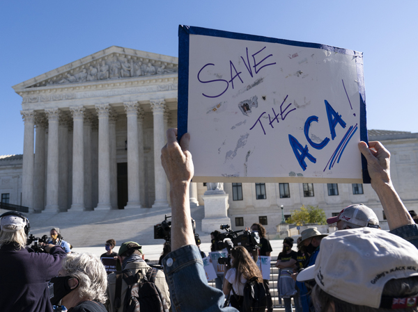 A demonstrator holds a sign in support of the Affordable Care Act in front of the U.S. Supreme Court last November. On Thursday, the justices did just that.