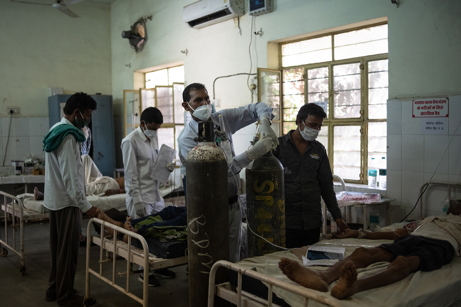 Medical attendant Gurmesh Kumawat prepares to administer supplemental oxygen to a coronavirus patient in the emergency ward at the BDM Government Hospital in mid-May in Kotputli, India. (Rebecca Conway/Getty Images)