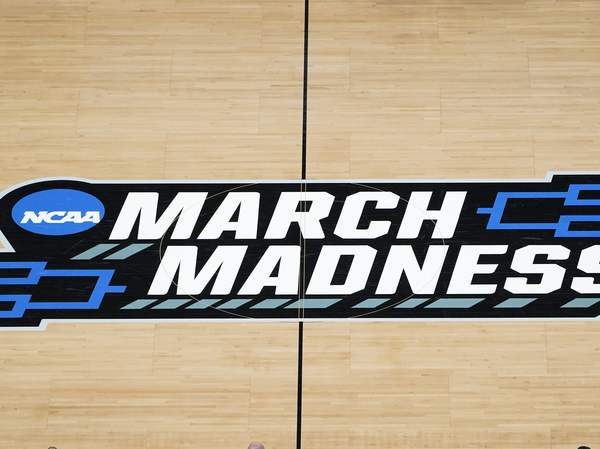 The March Madness logo is shown on the court during the first half of a men's college basketball game in the first round of the NCAA tournament at Bankers Life Fieldhouse in Indianapolis. The Supreme Court eroded the difference between elite college athletes and professional sports stars.