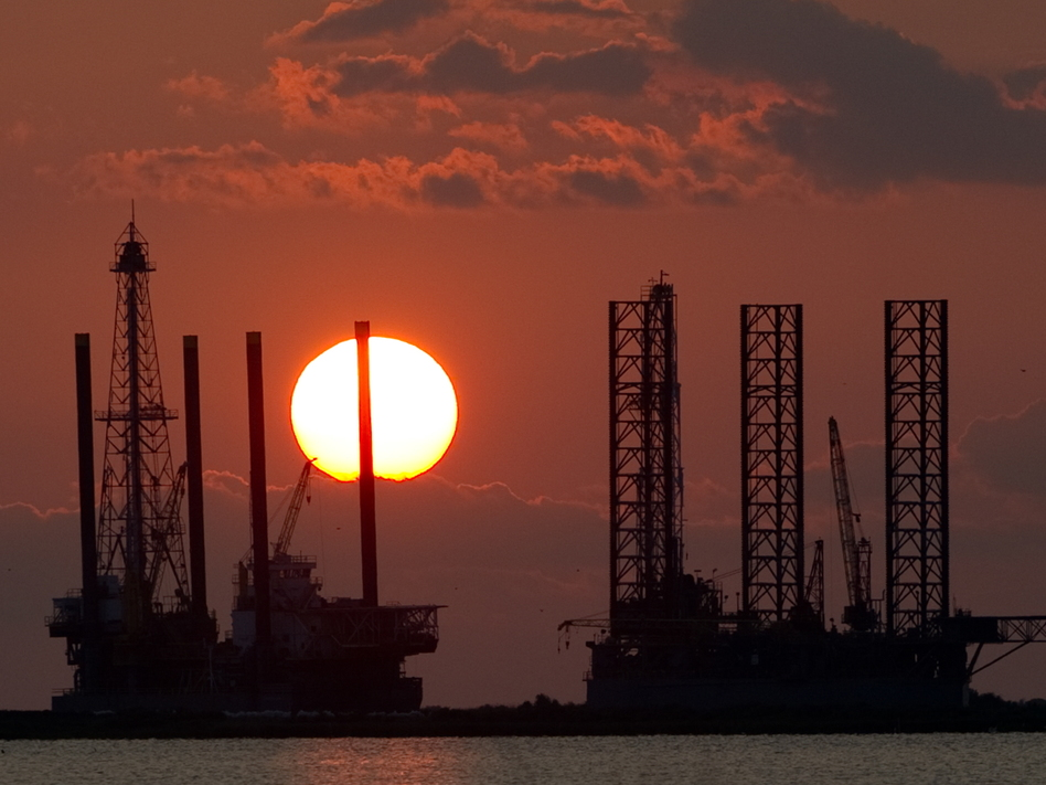 The energy industry was shaken by a trio of events this week that could help shape the future of oil and gas. Here, the sun sets behind two under-construction offshore oil platform rigs in Port Fourchon, La., in 2010. (Saul Loeb/AFP via Getty Images)