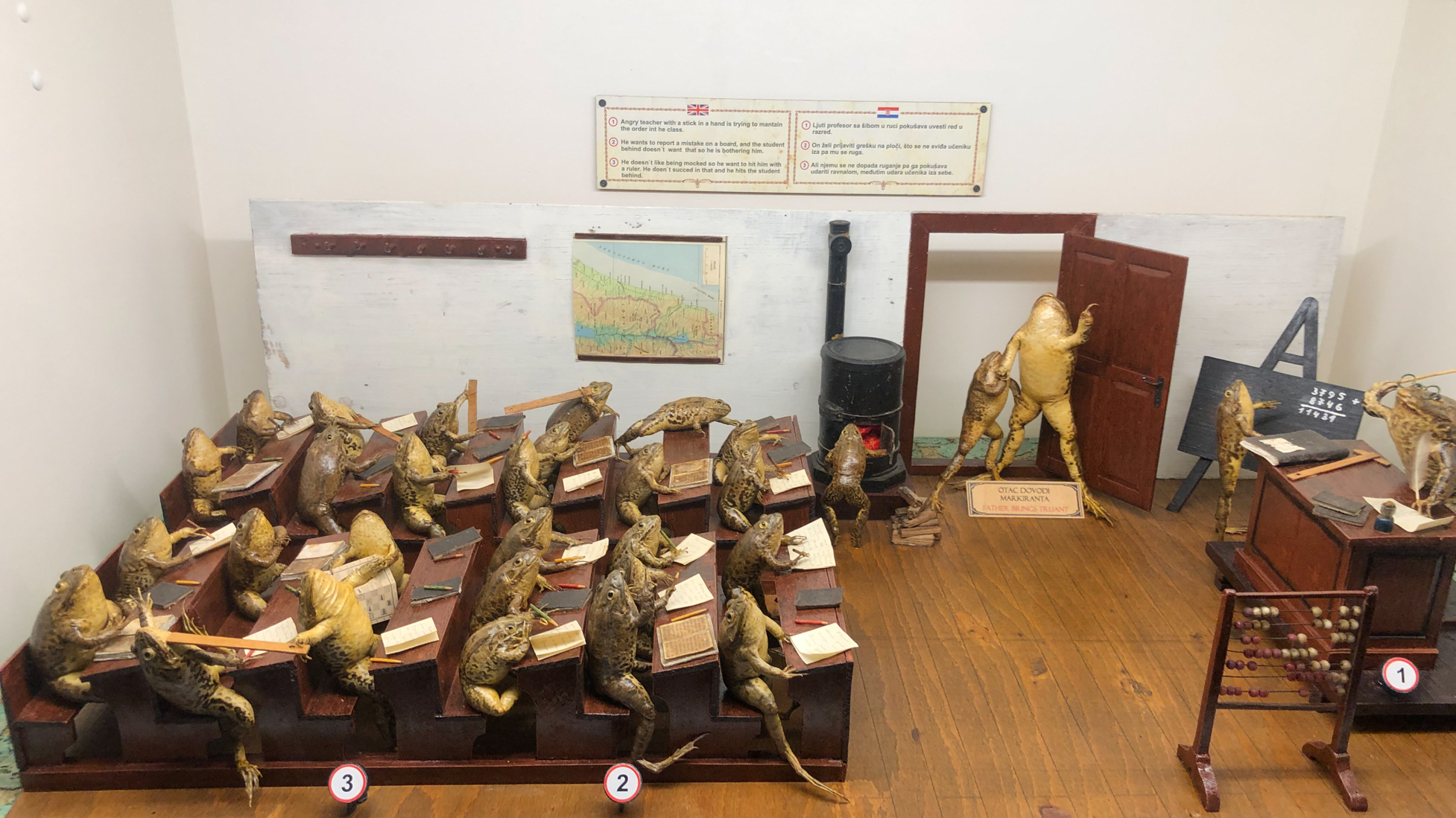 A Froggyland diorama shows a teacher trying to control a class in which students are hitting each other with rulers, arriving late to class and balancing pencils on their noses. Each  diorama displays anthropomorphized frogs in human scenes of the early 20th century.