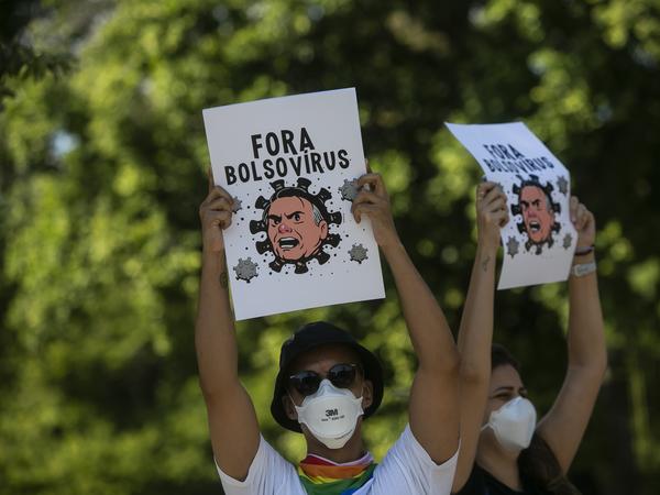 Manifestantes usando máscaras protetoras seguram cartazes retratando o presidente Jair Bolsonaro como um vírus de protesto contra a resposta do governo no combate à COVID-19, exigindo o impeachment de Bolsonaro, no Rio de Janeiro, Brasil, sábado, 29 de maio de 2021.