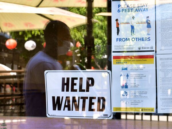 """A """"Help Wanted"""" sign is posted beside coronavirus health safety guidelines at a restaurant in Los Angeles on May 28. Businesses are desperate for workers even as millions remain unemployed. Republican governors blame a major unemployment benefit passed during the pandemic, saying it's dissuading people from rejoining the workforce."""