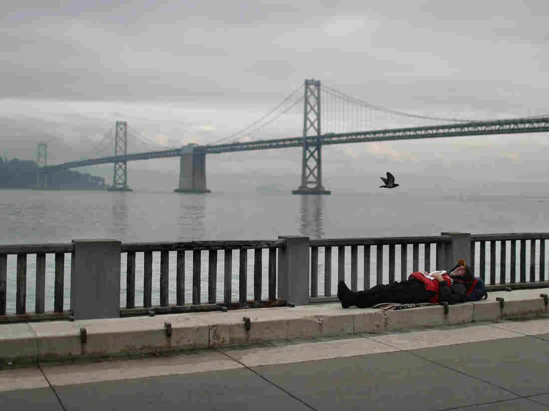 A homeless man sleeps on the sidewalk near the San Francisco–Oakland Bay Bridge in December 2019.