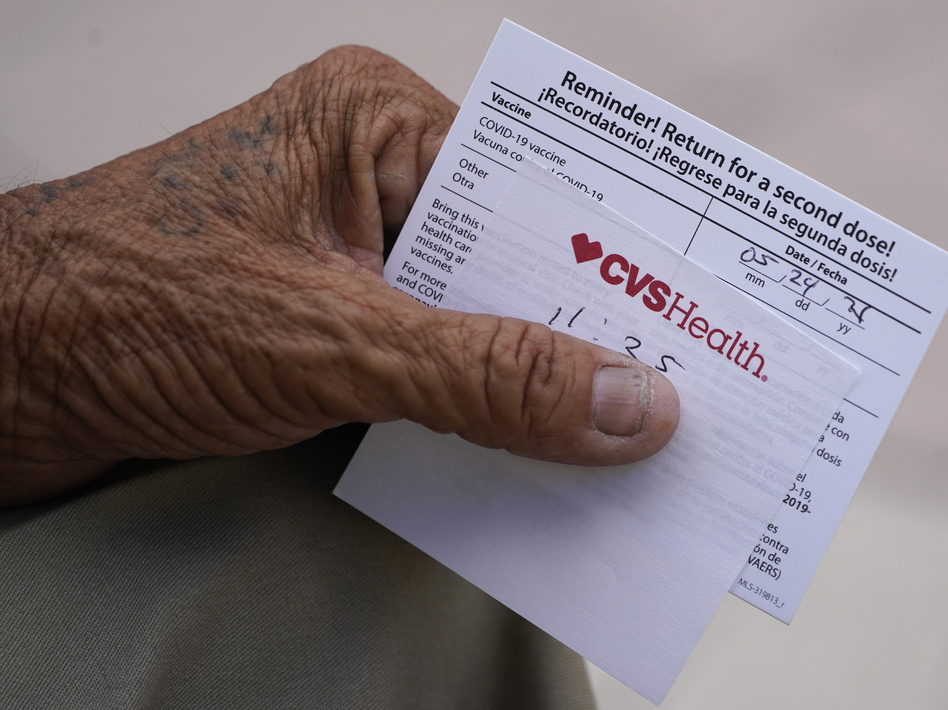 A man holds his vaccination reminder card after having received his first shot at a pop-up vaccination site next to Maximo Gomez Park, also known as Domino Park, on May 3 in the Little Havana neighborhood of Miami. (Wilfredo Lee/AP)
