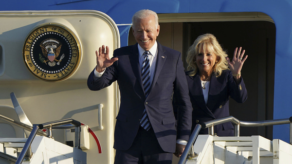 President Joe Biden and First Lady Jill Biden wave as they arrive in England ahead of the G7 summit on Wednesday.
