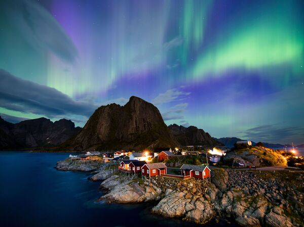 The northern lights (aurora borealis) illuminate the sky over Reinfjorden in Reine, on Lofoten Islands in the Arctic Circle in 2017.