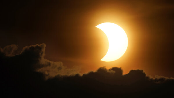 The sun is partially eclipsed as it rises over lower Manhattan in New York on Thursday.