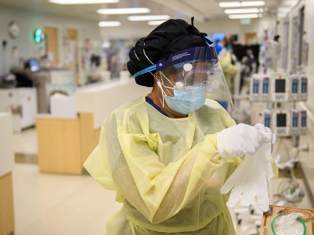 Uma enfermeira veste equipamento de proteção individual para cuidar de um paciente em uma unidade de terapia intensiva Covid-19 no Hospital Comunitário Martin Luther King Jr. em Los Angeles.