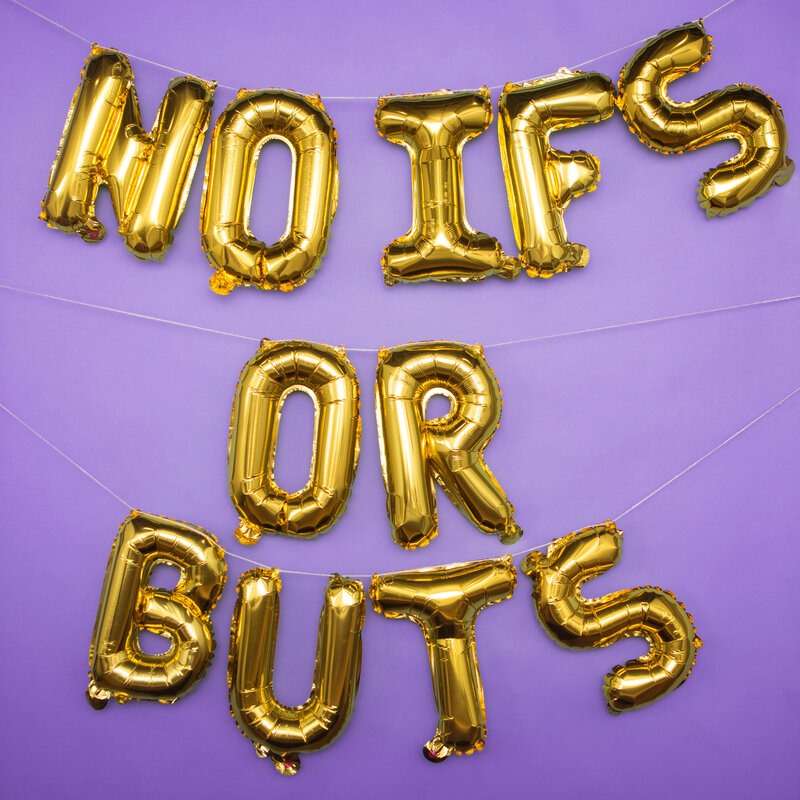 """Gold foil balloon letters spelling out """"no ifs or buts"""" are strung up in front of a purple backdrop."""