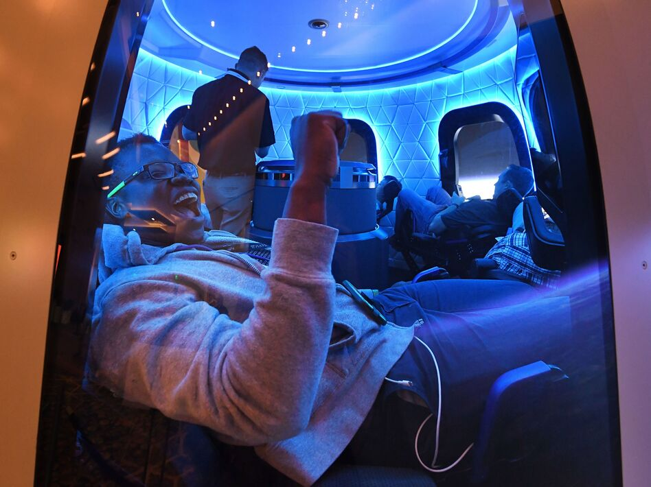 Participants sit a Blue Origin space simulator during a conference on robotics and artificial intelligence in Las Vegas on June 5, 2019. On Saturday, Blue Origin announced that an unidentified bidder will pay $28 million for a suborbital flight on the company's New Shepard vehicle. (Mark Ralston/AFP via Getty Images)