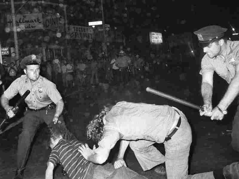 A New York Police officer grabs a man by the hair as another officer clubs a man during a confrontation in Greenwich Village after a Gay Power march in New York. A year earlier, young gays, lesbians and transgender people clashed with police near a bar called The Stonewall Inn.