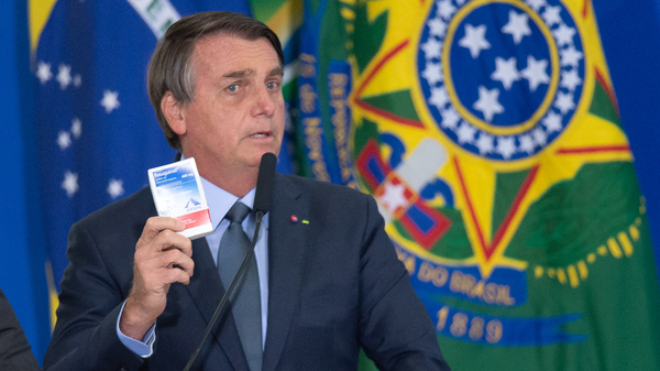 """Brazilian President Jair Bolsonaro holds up a box of chloroquine, an antimalarial medicine that his administration endorsed as part of an """"early treatment"""" strategy for COVID-19. There is no evidence the drug can prevent the coronavirus or reduce the severity of symptoms."""