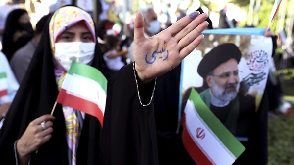 A supporter of presidential candidate Ebrahim Raisi shows her hand with writing in Persian that reads