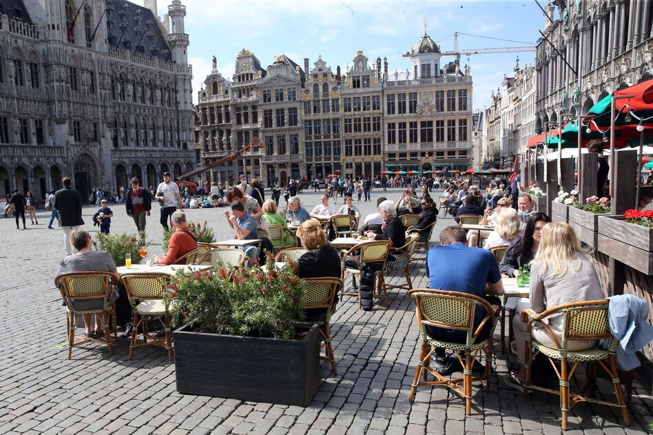 People enjoy the May sunshine from the cafe terraces of Brussels' Grand Place. On Friday, European Union added the United States to the list of countries whose citizens and residents should be allowed to travel freely within the bloc. (Francois Walcshaerts/AFP via Getty Images)