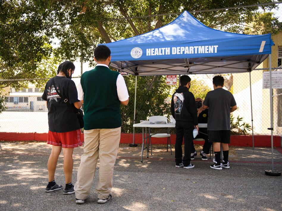 Teenagers get vaccination cards after receiving a first dose of the Pfizer COVID-19 vaccine last month at a mobile clinic at the Weingart East Los Angeles YMCA in Los Angeles.