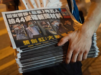 """A man buys multiple copies of the latest Apple Daily newspaper in Hong Kong. Police raided the office of Apple Daily, the city's fierce pro-democracy newspaper, in an operation involving more than 200 officers. Secretary for Security John Lee said the company used """"news coverage as a tool"""" to harm national security, according to local media reports."""