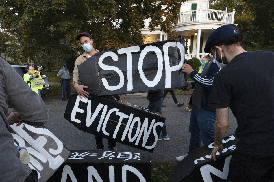 Housing activists erect a sign in front of Massachusetts Gov. Charlie Baker's house in Swampscott, Mass., on Oct. 14, 2020. The Centers for Disease Control and Prevention has extended a moratorium on evictions until the end of July. (Michael Dwyer/AP)