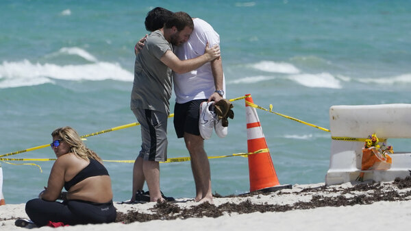 Two men console each other on the beach Sunday near the site of the Champlain Towers South condo building in Surfside, Fla. Rescuers kept digging through the mound of rubble over the weekend, clinging to hope that someone could be found alive.