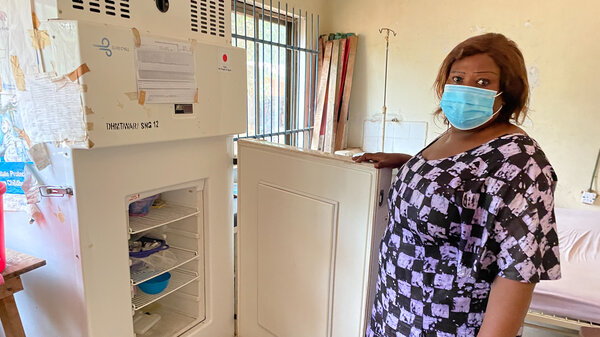 """Mariama Koroma shows a revolutionary type of solar-powered refrigerator in the Songo Health Clinic, used to store vaccines. They don't use batteries but use a """"direct-drive"""" system to store coldness."""