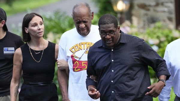 Bill Cosby (center) approaches members of the media gathered outside his home in Cheltenham, Pa., with his spokesperson Andrew Wyatt. On Wednesday, Pennsylvania