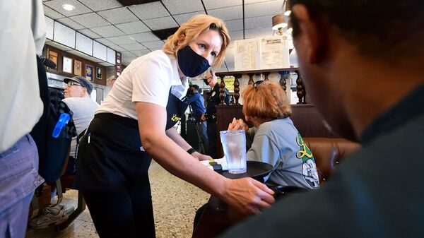 A waitress wears a face mask while serving at Langer's Delicatessen-Restaurant in Los Angeles on June 15.