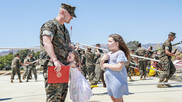 Joseph Hardebeck, a senior Navy corpsman, is greeted by his daughters Zoey, 9, and Adalie, 7, after receiving the Purple Heart at an award ceremony at Southern California
