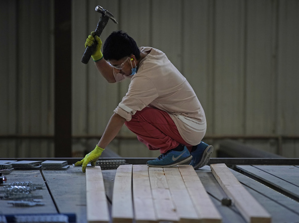 A worker in Spanish Fork, Utah, assembles a truss for a home on May 12. The surge in lumber prices was seen by some economists as another example of potentially rampant inflation. Instead, prices fell.
