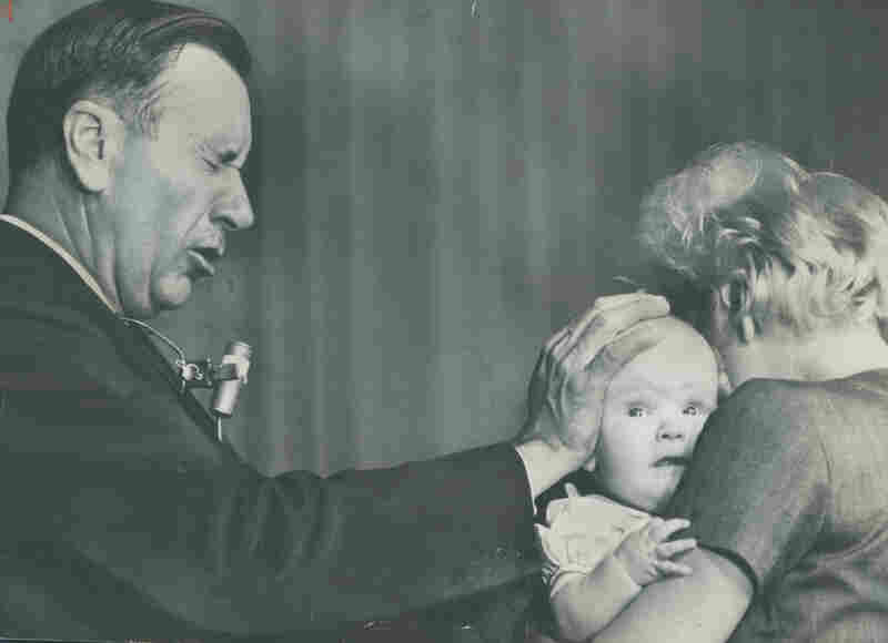 Evangelist Oral Roberts seen praying for the healing of a baby in 1964.