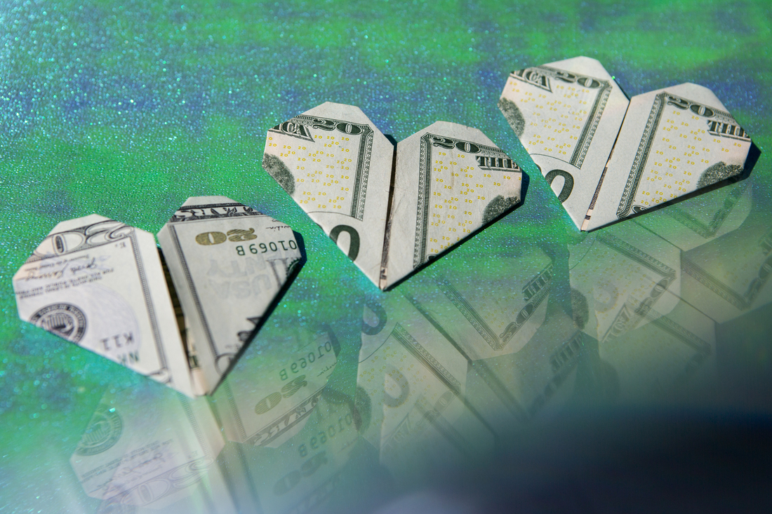 Three dollar bills folded into hearts are displayed on a sparkly green and blue background. A reflection of the money is seen in the bottom right corner of the frame.