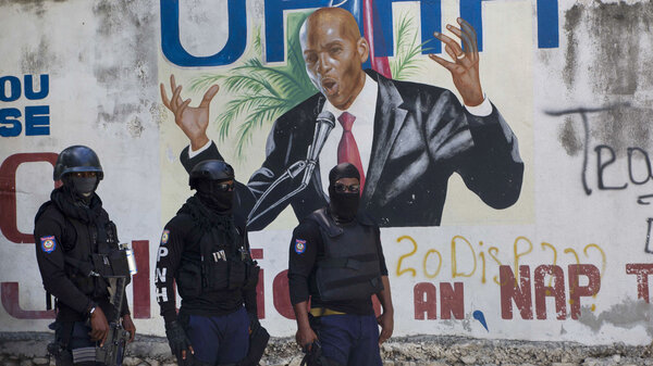 Police stand near a mural featuring Haitian President Jovenel Moise, near the leader's residence where he was killed by gunmen in the early morning hours in Port-au-Prince on Wednesday.