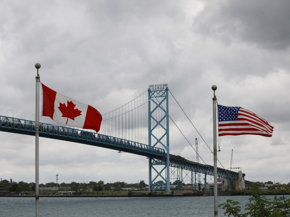 Canadian and American flags fly near the Ambassador Bridge connecting Canada to the U.S. in Windsor, Ontario, in May. Half of respondents in a poll of Canadians this month by Nanos Research said restrictions on travel across the U.S.-Canada border should not be eliminated until this fall or next year. (Cole Burston/Bloomberg via Getty Images)
