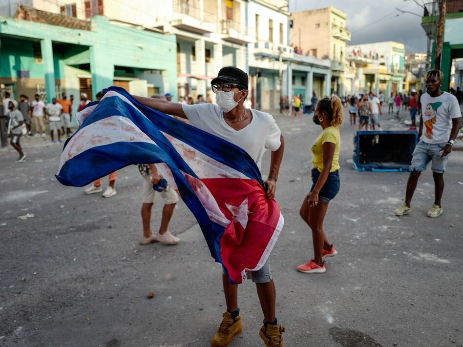 A man waves a Cuban flag during a demonstration against Cuban President Miguel Díaz-Canel's government Sunday in Havana as large numbers take part in rare protests against the communist regime. (Adalberto Roque/AFP via Getty Images)