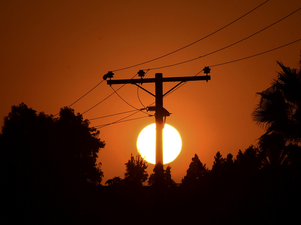 The sun sets behind power lines in Los Angeles in September.