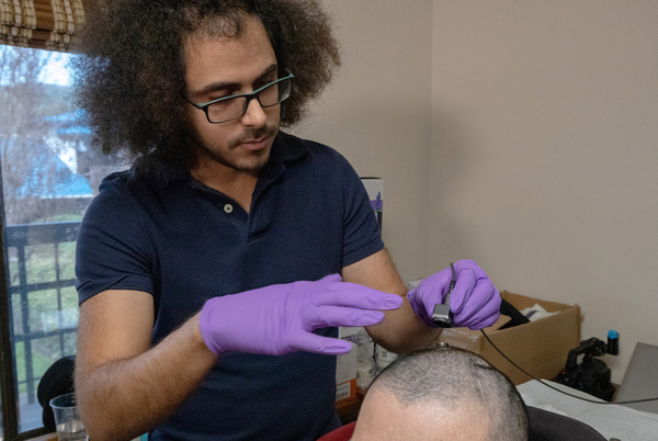 University of California, San Francisco researcher David Moses works with the trial participant identified only as BRAVO1 to measure brain activity while he attempts to produce words and sentences.