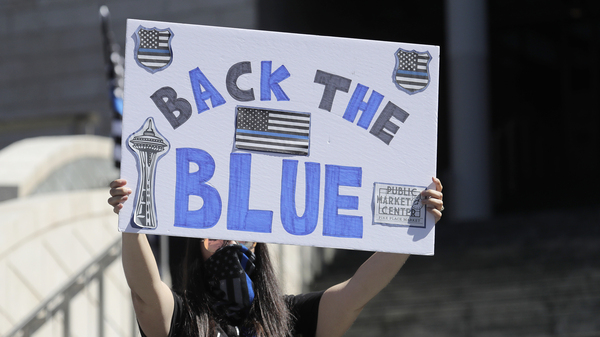 """A person holds a """"Back the Blue"""" sign in support of police during a 2020 rally in front of Seattle City Hall."""