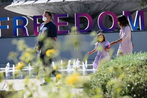People enjoy an outdoor art exhibition in downtown Los Angeles in early July. Los Angeles County public health authorities are now urging unvaccinated and vaccinated people alike to wear face coverings in public indoor spaces because of the growing threat posed by the more contagious delta variant of the coronavirus.