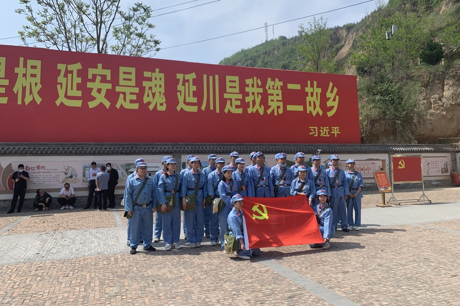 Tourists dressed up as People's Liberation Army soldiers pose in Liangjiahe village, where a teenage Xi Jinping spent seven years doing hard labor. Today the village is a popular red tourism site. The sign displays a quote from Xi:
