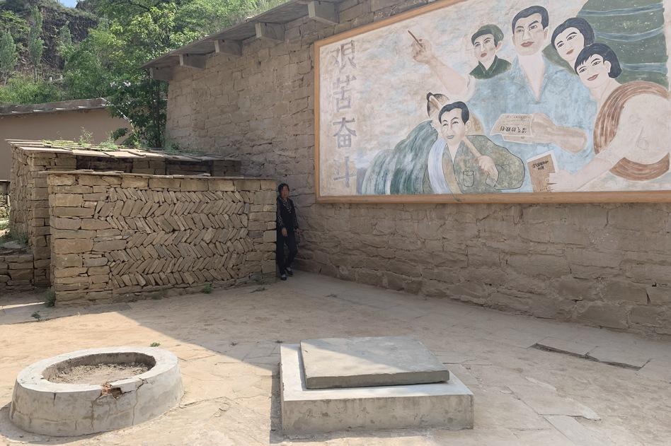 A natural gas fermentation chamber that Xi Jinping is said to have dug with his own hands while serving seven years' hard labor in Liangjiahe during the Cultural Revolution. The mural depicts peasants encouraging their fellow farmers to persevere through hardship.