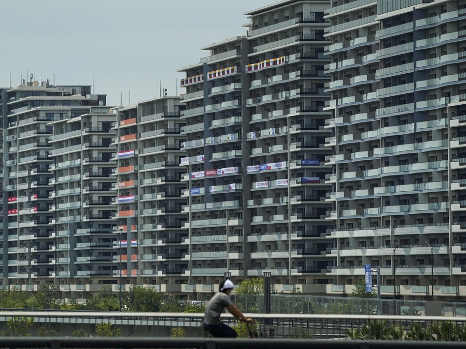 A man rides a bike near the village for the Summer Olympics in Tokyo. On Saturday, officials announced the first case of COVID-19 found at the center housing thousands of athletes. (Jae C. Hong/AP)