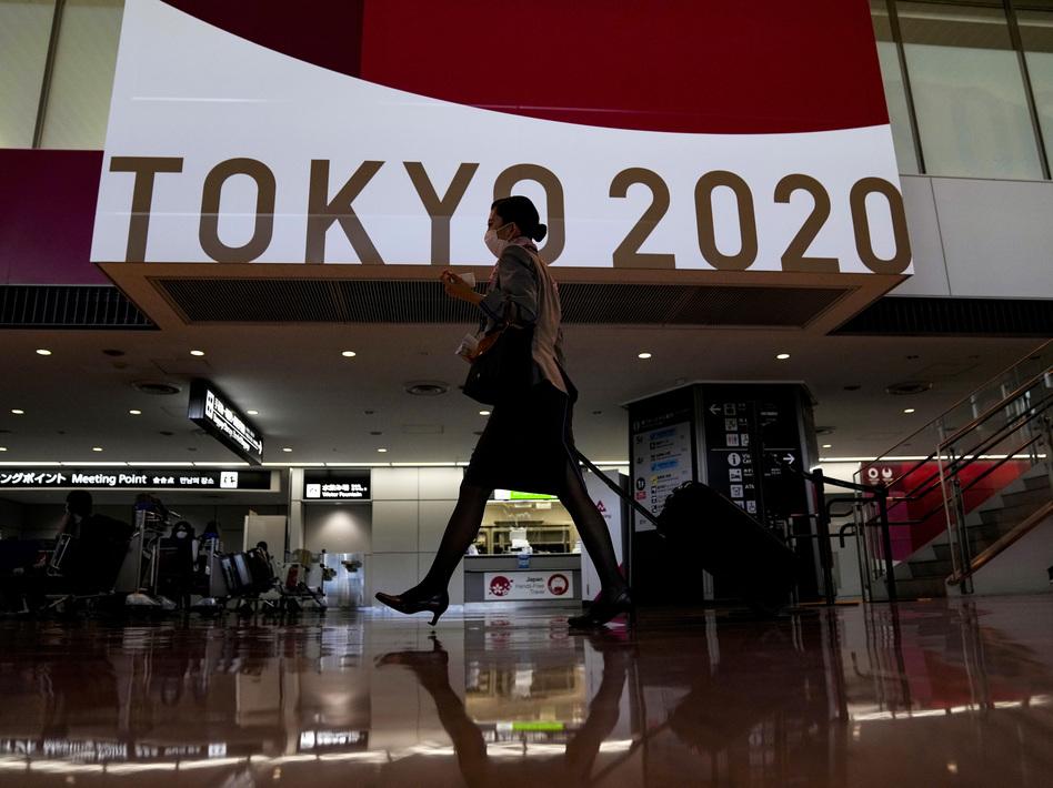A flight attendant walks by a large display of Tokyo 2020 Olympics at Narita International Airport on Thursday in Narita, east of Tokyo. (Kiichiro Sato/AP)