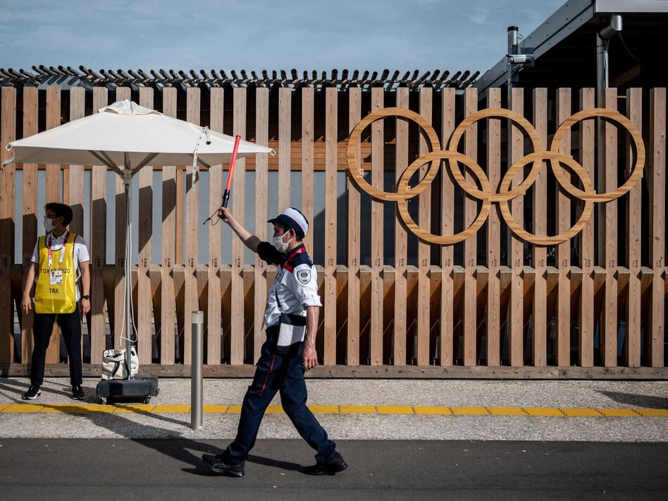 A staff member guides a taxi at one of the entrances at the Olympic and Paralympic Village in Tokyo. (Philip Fong/AFP via Getty Images)