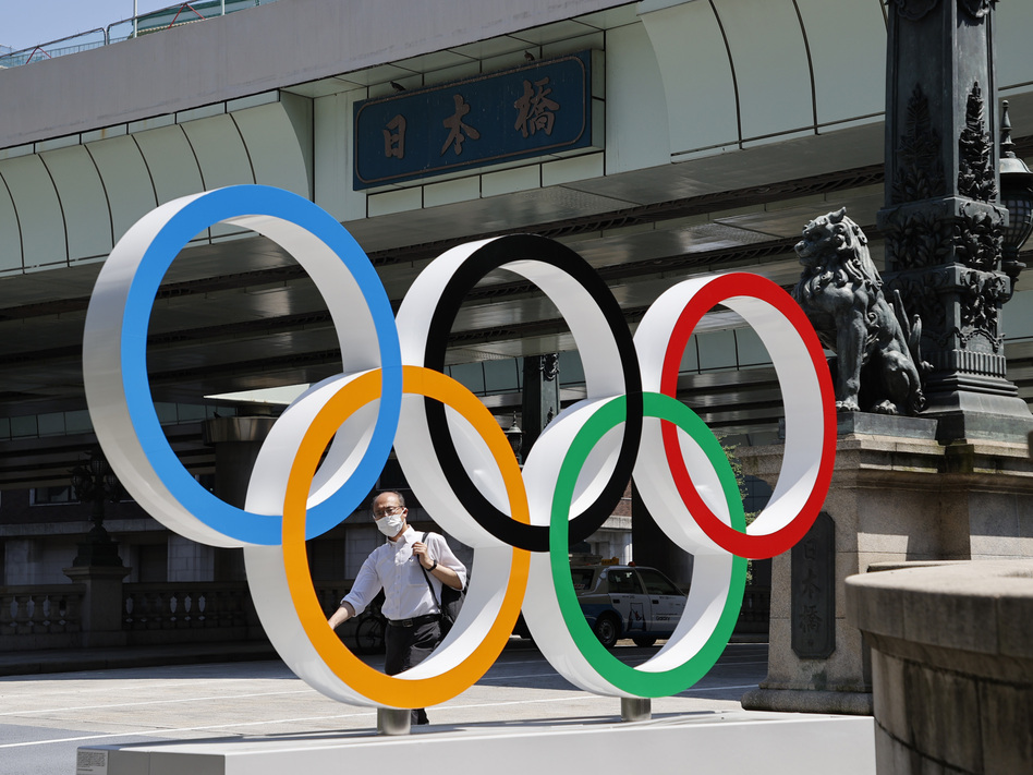 A man wearing a face mask walks past the Olympic Rings ahead of the Tokyo 2020 Olympic Games. The Games are scheduled to begin this week in Japan despite a global rise in coronavirus cases. (Toru Hanai/Getty Images)