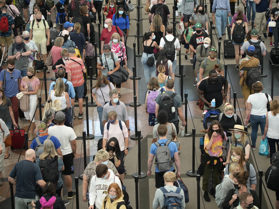 In this June 16, 2021 file photo, travelers queue up in long lines to pass through the south security checkpoint in Denver International Airport in Denver. (David Zalubowski/AP)