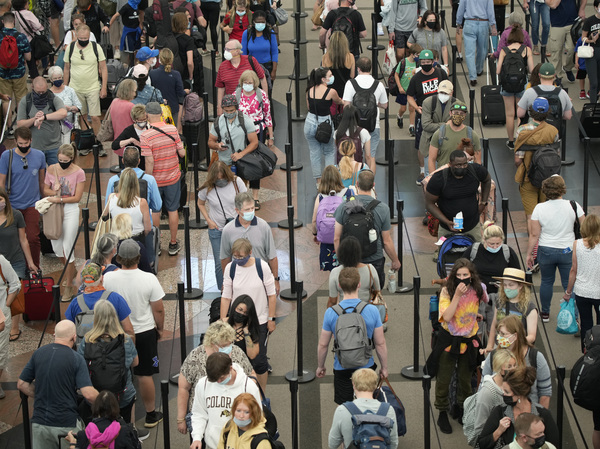 In this June 16, 2021 file photo, travelers queue up in long lines to pass through the south security checkpoint in Denver International Airport in Denver.