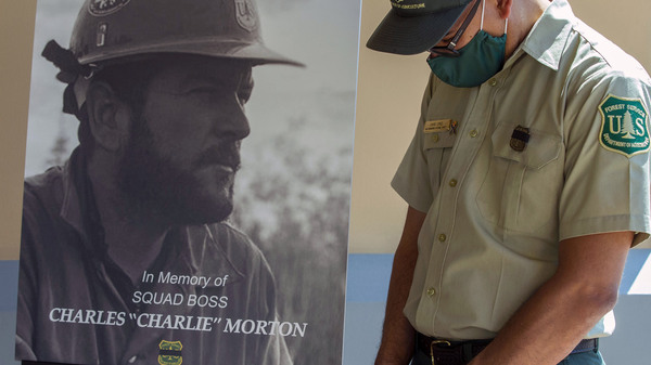 San Bernardino National Forest firefighter David Cruz lowers his head during a memorial for Charles Morton, who was killed while fighting the El Dorado Fire last year.