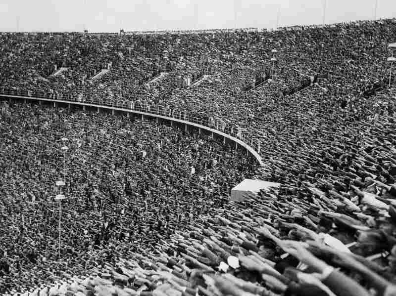 Spectators in the crowd at the 1936 Olympic Games in Berlin raise their hands in the Nazi salute in tribute to Hitler's arrival at the stadium.