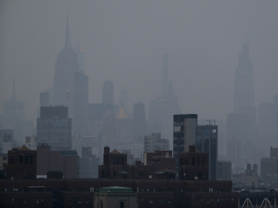 A thick haze hangs over Manhattan on Tuesday. Wildfires in the West, including the Bootleg Fire in Oregon, are creating hazy skies and poor air quality as far away as the East Coast. (Julie Jacobson/AP)