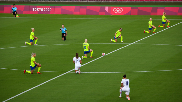 Players and officials take a knee just before the start of Wednesday's match between the U.S and Swedish women's soccer teams.
